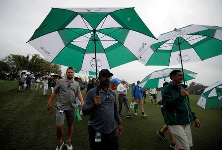 Patrons leave as play is suspended during the Par 3 Tournament at Augusta National Golf Club in Augusta, California, U.S., April 5, 2017. REUTERS/Lucy Nicholson