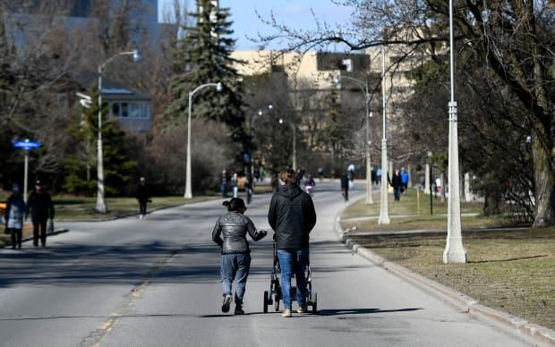 People walk along the Queen Elizabeth Driveway in Ottawa April 18, 2020, after it was closed to motor vehicle traffic to allow people to get outdoors safely. A portion of the driveway will open for people to exercise on this coming weekend. (Justin Tang/Canadian Press - image credit)