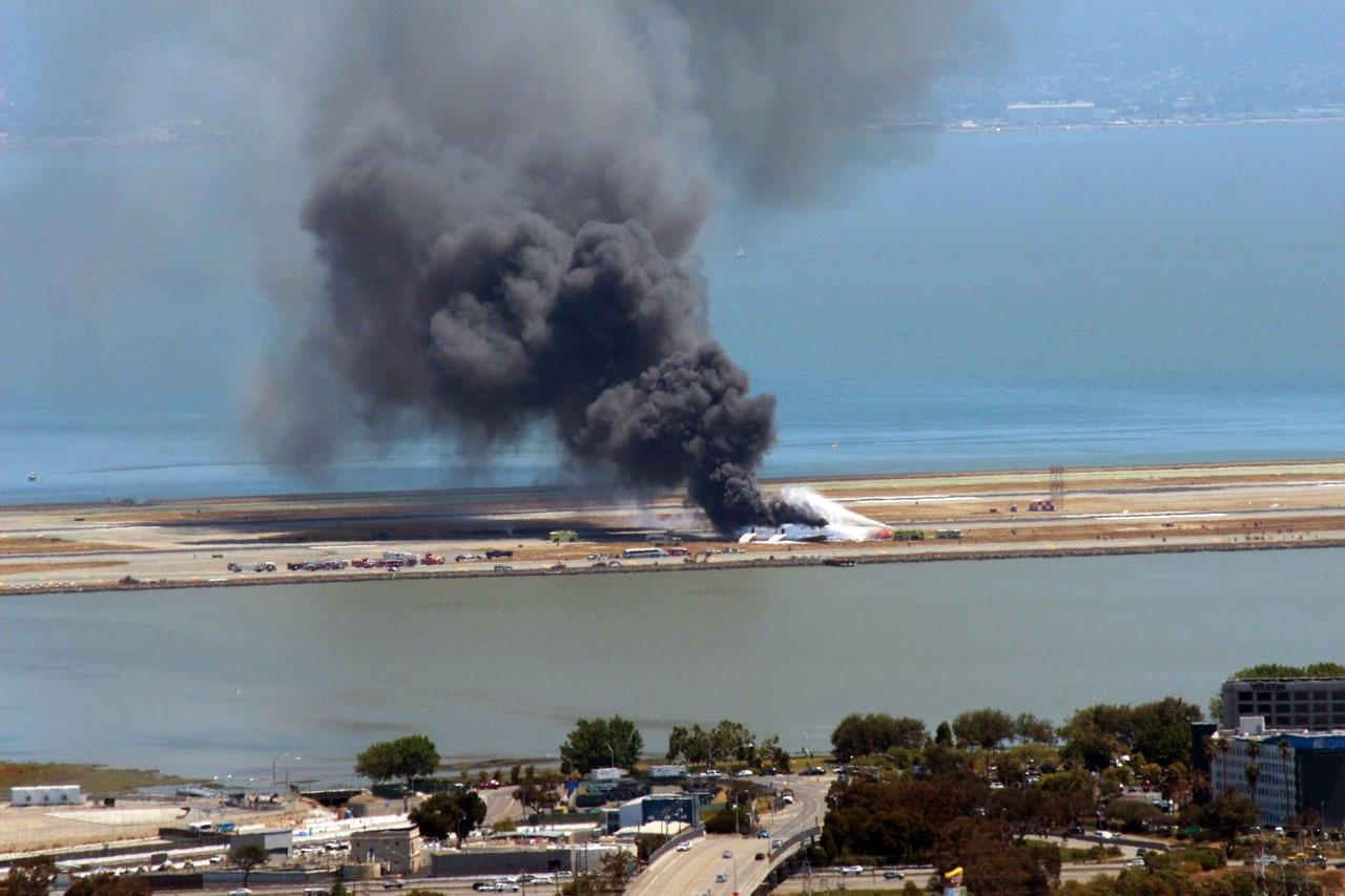 This photo provided by Dawn Siadatan shows Asiana Airlines flight 214 just moments after crashing at the San Francisco International Airport in San Francisco, Saturday, July 6, 2013. The Asiana Airlines Boeing 777 crashed while landing after a likely 10-hour-plus flight from Seoul, South Korea. The flight originated in Shanghai and stopped in Seoul before the long trek to San Francisco. (AP Photo/Dawn Siadatan)