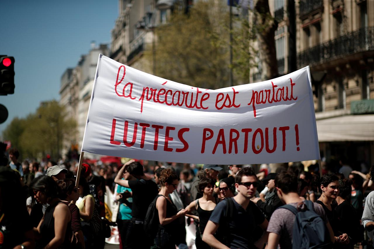 "Protesters hold a banner reading ""Precarity is everywhere, conflict everywhere"" during a demonstration against the French government's reform plans in Paris as part of a national day of protest, France, April 19, 2018.  REUTERS/Benoit Tessier"