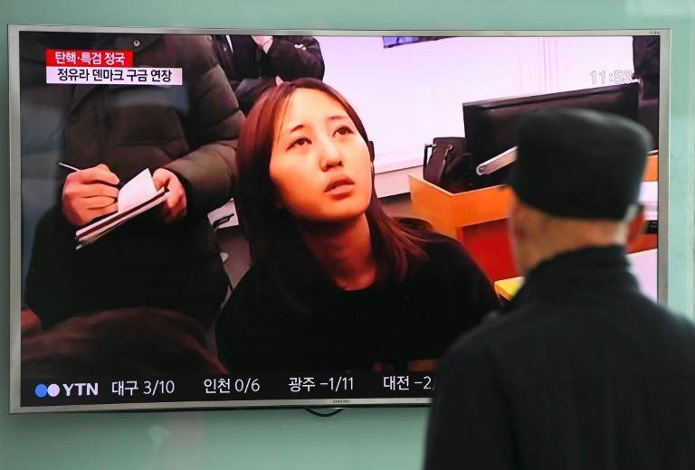 """People at a railway station in Seoul look at a news report on the arrest of Chung Yoo-Ra, the 20-year-old daughter of the woman dubbed South Korea's """"Rasputin"""", on January 3, 2017"""