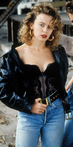 <b>Kylie in The Delinquents, 1989</b><br><br>Kylie showed off a more rebellious look in this revealing corset and high waisted bleach-wash jeans outfit for the film, finishing the look with a pair of gold hoop earrings, leather bomber jacket and a waisted belt.