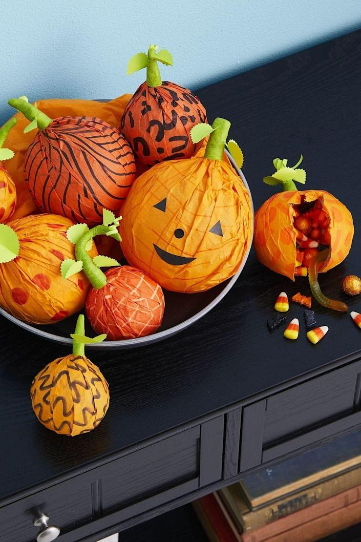"""<p>To make these sweet pumpkin treats for your guests, fill clear plastic ornament balls with candy. Then, use brush-tip Sharpie to draw patterns on orange tissue paper. Wrap tissue over ball, twist ends into a stem, and secure with green floral tape, tucking in green paper leaves as you wrap. To make pumpkin faces, glue on simple shapes cut out of construction paper.</p><p><a class=""""link rapid-noclick-resp"""" href=""""https://www.amazon.com/Fillable-Removable-Christmas-Ornaments-XMasDecor/dp/B08Q3RHW44?tag=syn-yahoo-20&ascsubtag=%5Bartid%7C10070.g.1908%5Bsrc%7Cyahoo-us"""" rel=""""nofollow noopener"""" target=""""_blank"""" data-ylk=""""slk:SHOP PLASTIC ORNAMENTS"""">SHOP PLASTIC ORNAMENTS</a></p>"""