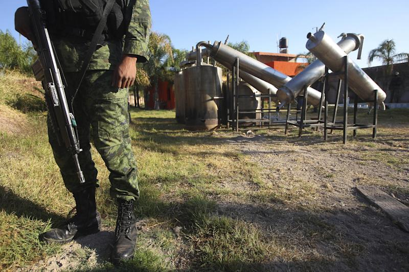 "FILE - In this Feb. 9, 2012, file photo a soldier stands in what was identified as ""metal reactors"" after a seizure of a large clandestine methamphetamine lab at a ranch in Tlajomulco de Zuniga, on the outskirts of Guadalajara, Mexico. Soldiers made a historic seizure, 15 tons of pure methamphetamine, a haul that could have supplied 13 million doses worth over $4 billion. (AP Photo/Bruno Gonzalez, File)"