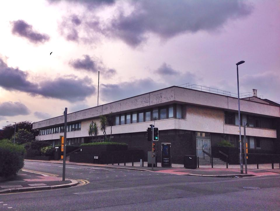 Hove, United Kingdom - May 30 , 2015 Long shot of the Holland Road Hove Trial Centre against a dusk sky and a seagull flying past. This was taken in the evening when the court is closed and depicts solely the external public building from across the crossroads with its flagpole, crest and entrance stairwells.