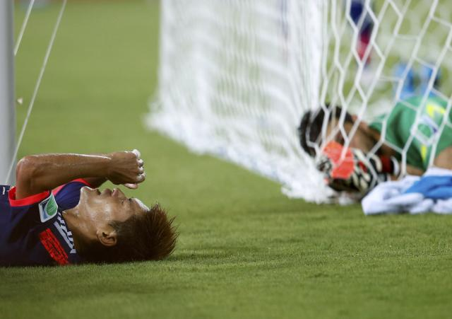 Japan's Yoshito Okubo (L) lies on the ground after failing to score a goal as Greece's goalkeeper Orestis Karnezis looks on during their 2014 World Cup Group C soccer match at the Dunas arena in Natal June 19, 2014. REUTERS/Toru Hanai (BRAZIL - Tags: SOCCER SPORT WORLD CUP TPX IMAGES OF THE DAY)
