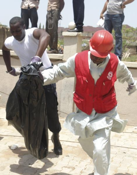 Rescuers remove body parts at the bombed office of ThisDay, an influential daily newspaper in Abuja, Nigeria, Thursday, April. 26, 2012, A suicide bomber detonated a car loaded with explosives Thursday at the office of the major Nigerian newspaper in the country's capital and another man threw a bomb near another newspaper office in Kaduna, killing at least six people in the attacks, witnesses said. (AP Photos/Gbemiga Olamikan)