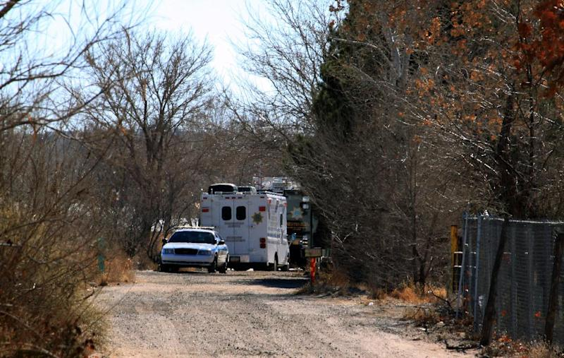 Bernalillo County authorities are stationed outside a home south of Albuquerque, N.M., on Sunday, Jan. 20, 2013, where two adults and three children were found shot to death. Authorities say a teenager has been arrested and booked on murder and other charges in connection with the shootings. (AP Photo/Susan Montoya Bryan)