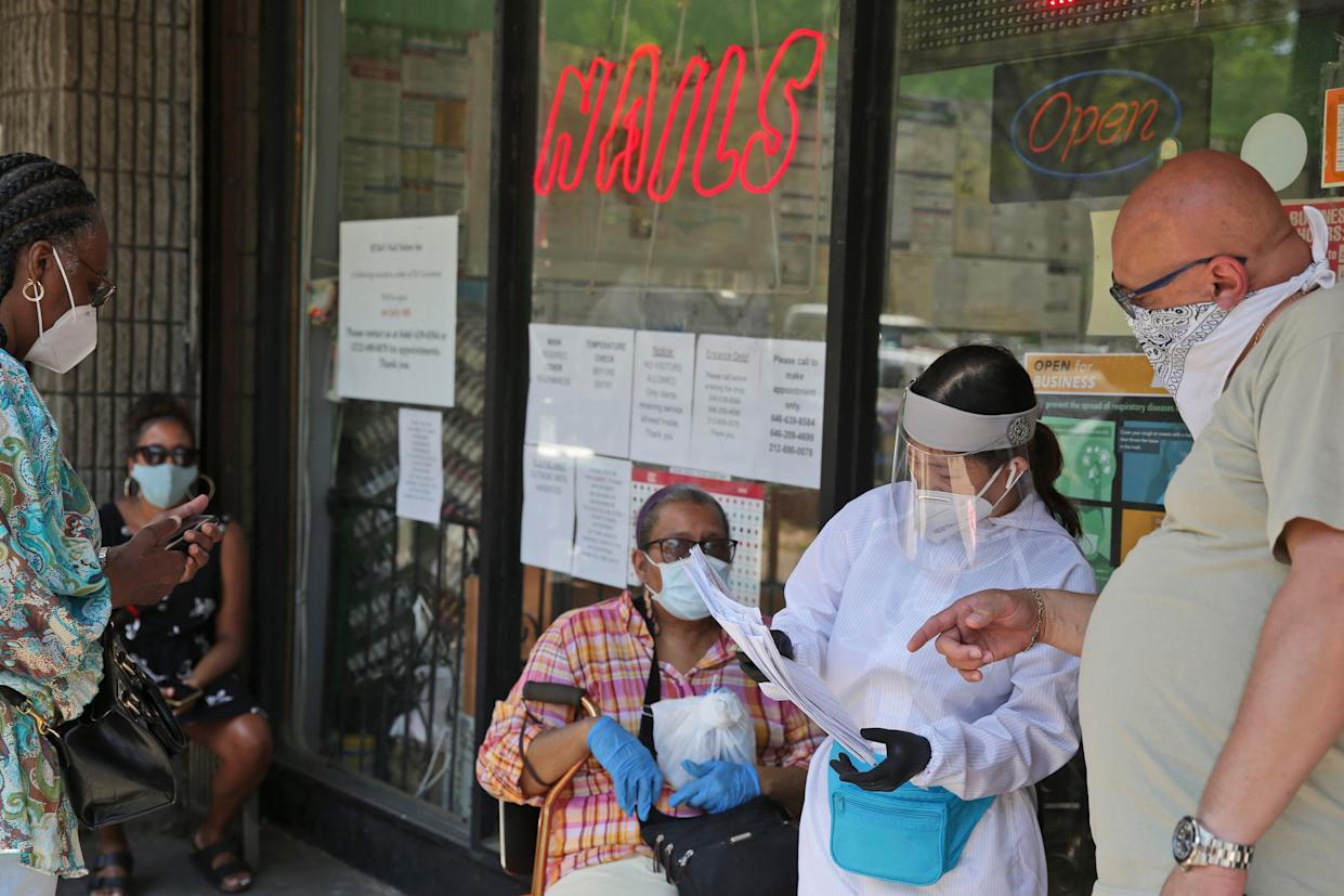 People try to figure out whose appointment is next while talking to an employee in front of HT&V; Nails in the Harlem section of New York on Monday, July 6, 2020. Nail salons and dog runs were back in business on Monday as New York City entered a new phase in the easing of coronavirus restrictions.