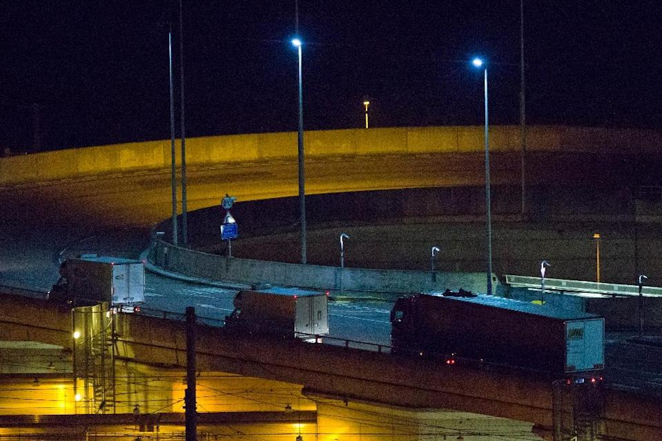 File picture shows two migrants clinging to the roof of a truck (R) as they arrive at the Eurotunnel terminal in the English city of Folkestone (AFP Photo/Justin Tallis)