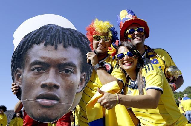Colombian supporters hold up a cutout portrait of current Colombian soccer player Juan Guillermo Cuadrado ahead of the group C World Cup soccer match between Colombia and Ivory Coast at the Estadio Nacional in Brasilia, Brazil, Thursday, June 19, 2014. (AP Photo/Sergei Grits)