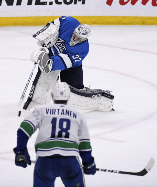 Winnipeg Jets goaltender Connor Hellebuyck (37) attempts a shot at the empty net as Vancouver Canucks' Jake Virtanen (18) watches during the third period of an NHL hockey game Tuesday, Jan. 14, 2020, in Winnipeg, Manitoba. (Fred Greenslade/The Canadian Press via AP)