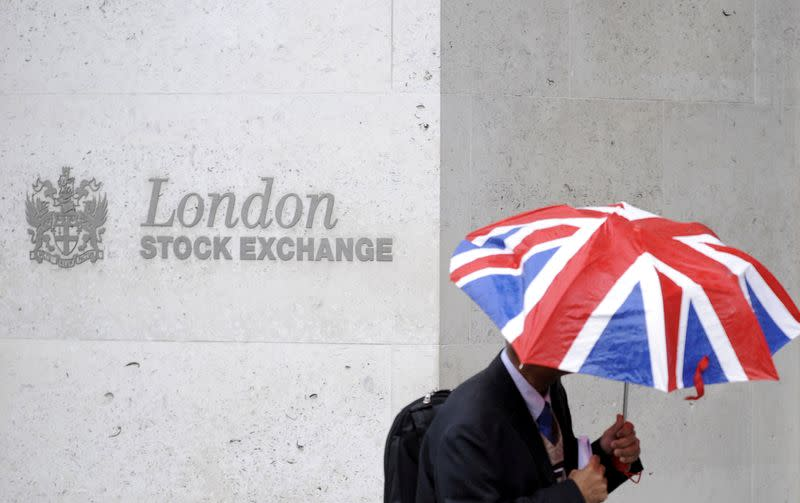 FILE PHOTO: A worker shelters from the rain as he passes the London Stock Exchange in the City of London
