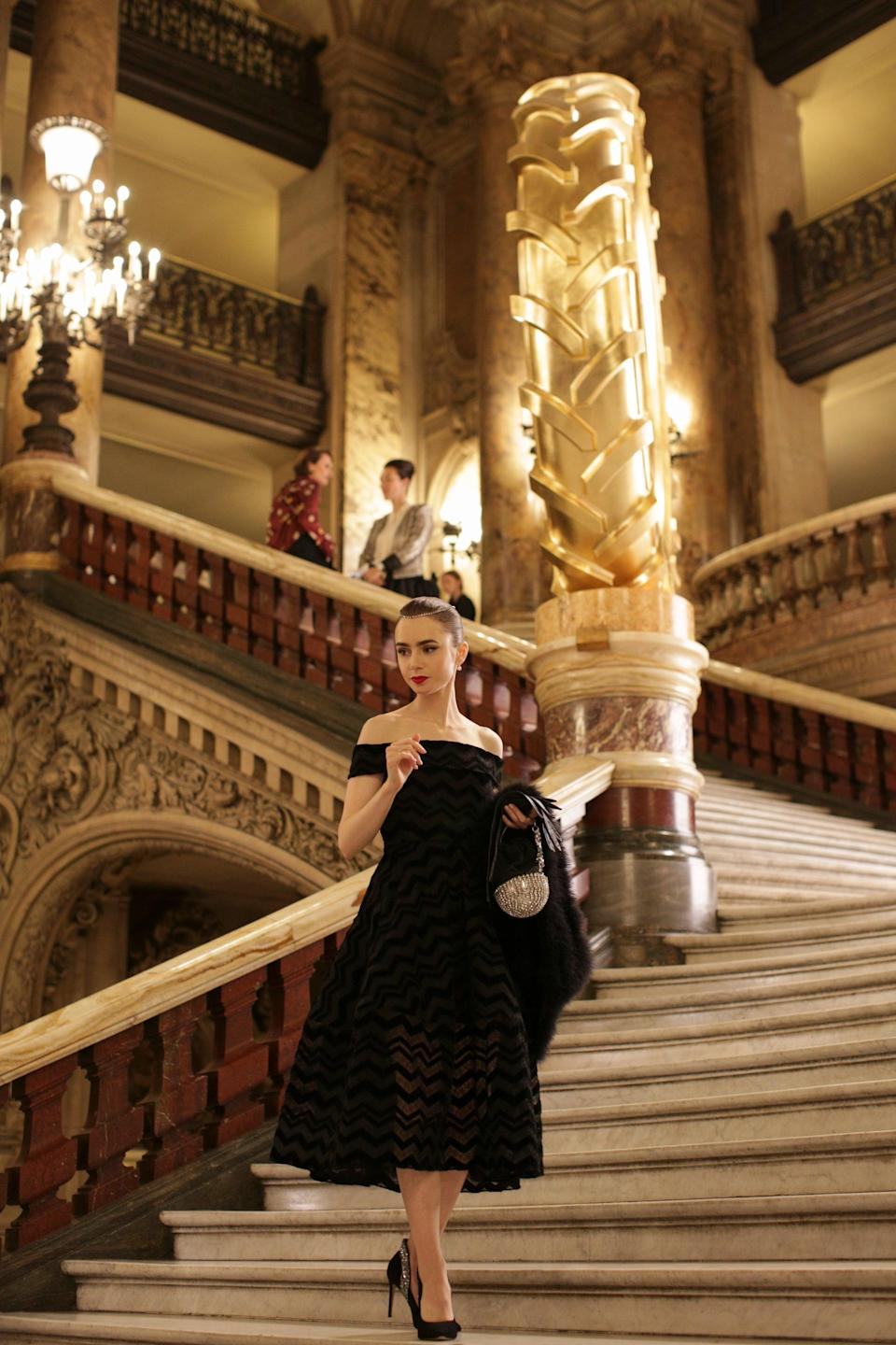 In an homage to Audrey Hepburn in <em>Funny Face</em>, Emily wears a stunning strapless black dress by Christian Siriano and crystal-adorned pumps to the opera. She rounds out the look with Agnelle gloves, vintage purse and fur, and La Compagnie du Costume jewels.