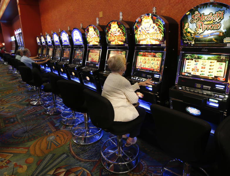 FILE--This photo from Thursday, Oct. 16, 2014 photo, show individuals playing video lottery terminals at Tioga Downs, in Nichols, N.Y. Revenues from three new upstate New York casinos have come in far slower than projected, meaning less money shared with local towns, cities and counties. (AP Photo/Mike Groll, File)