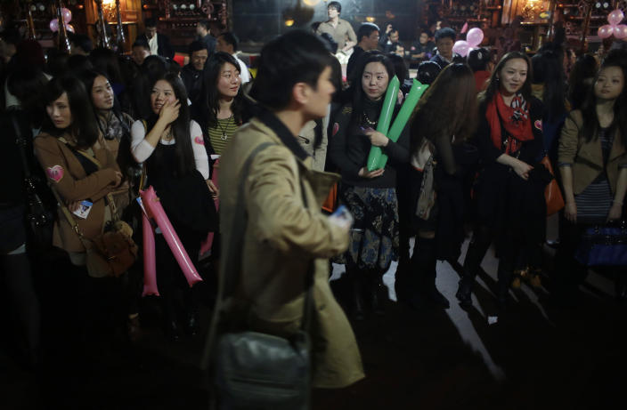 """Female participants who are singles wait to introduce themselves to male participants during a matchmaking party organized by one of the biggest Chinese matchmaking websites in Shanghai, China on Sunday Nov. 11, 2012. Singles Day was begun by Chinese college students in the 1990s as a version of Valentine's Day for people without romantic partners. The timing was based on the date Nov. 11, or """"11.11"""" — four singles. Unattached young people would treat each other to dinner or give gifts to woo that special someone and end their single status. (AP Photo/Eugene Hoshiko)"""