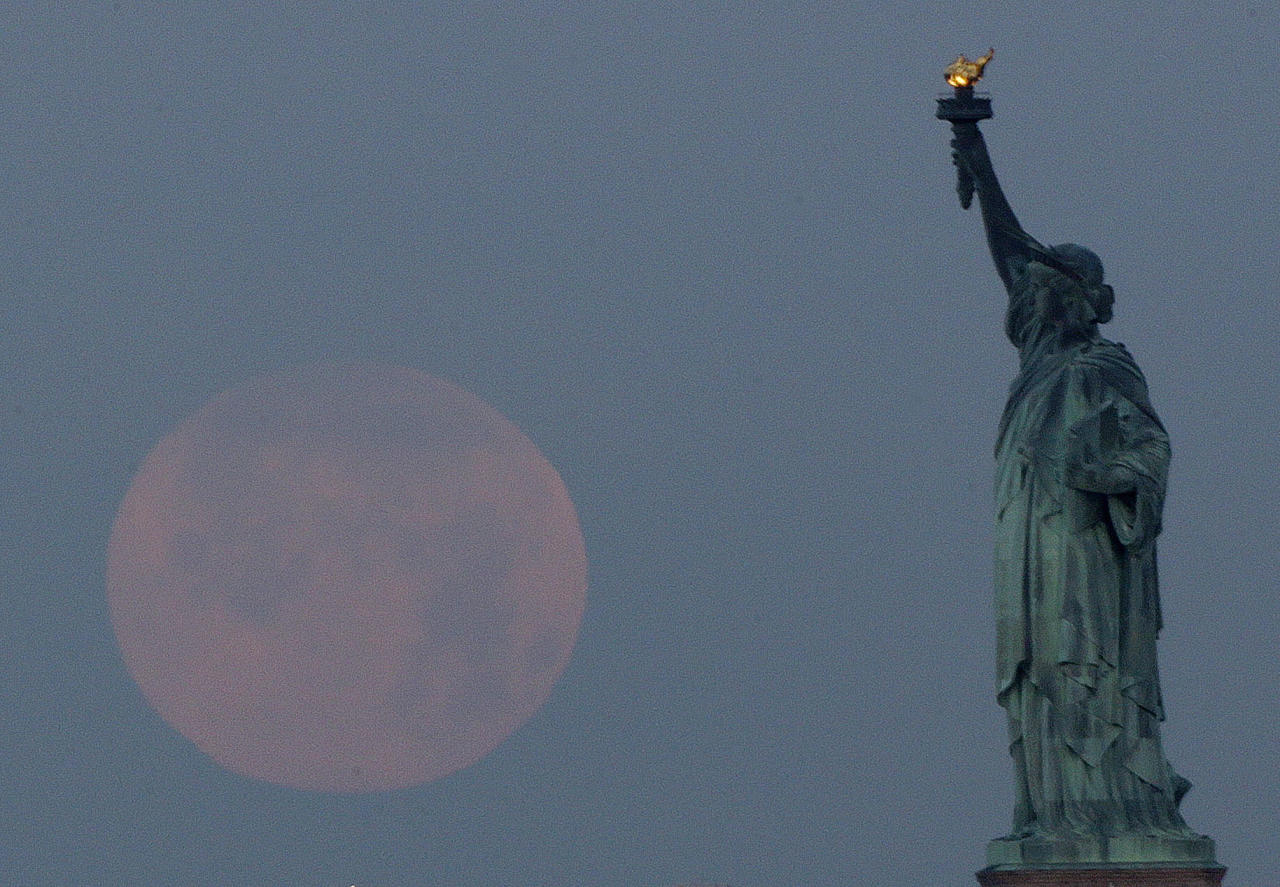 """A supermoon sets near the Statue of Liberty, Sunday, June 23, 2013, in New York. The larger than normal moon called the """"Supermoon"""" happens only once this year as the moon on its elliptical orbit is at its closest point to earth and is 13.5 percent larger than usual. (AP Photo/Julio Cortez)"""