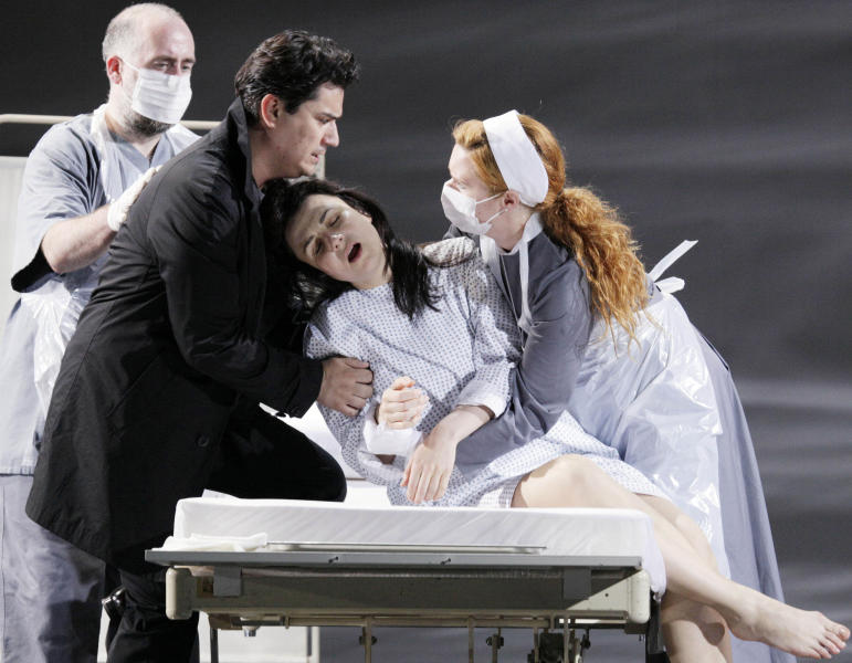 "In this picture taken Wednesday, May 23, 2012, Nenad Marinkovic in the role of Giuseppe, Saimir Pirgu as Alfredo Germont, Irina Lungu as Violetta Valery, and Claire Egan as Nun, from left, perform during a dress rehearsal at the Theater an der Wien in Vienna, Austria, for the opera ""La Traviata"" by Giuseppe Verdi. (AP Photo/dapd, Lilli Strauss)"