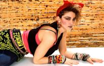 <p>Madonna wearing her signature rubber bracelets and cross jewelry for a photo shoot. </p>