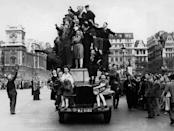 <p>Servicemen and citizens rejoice by way of riding a truck through the streets of London.</p>
