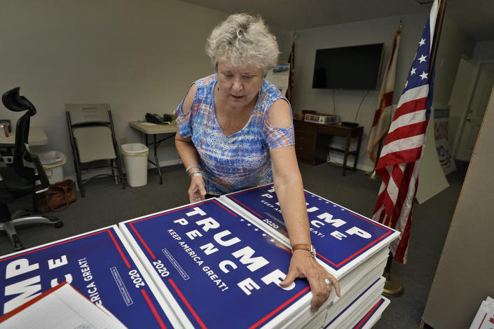 """FILE - In this Tuesday, Sept. 8, 2020 file phto, Pamela Allen organizes Trump-Pence campaign signs at the Pasco county GOP headquarters in Hudson, Fla. Allen, who worked as a poll watcher in Pasco County, said she saw no problems on Election Day. """"Here in Pasco I have to admit it was very well done,"""" she said. But she believes things she's seen on the conservative Donald Trump-favored Newsmax about alleged voter fraud in other states. (AP Photo/Chris O'Meara)"""