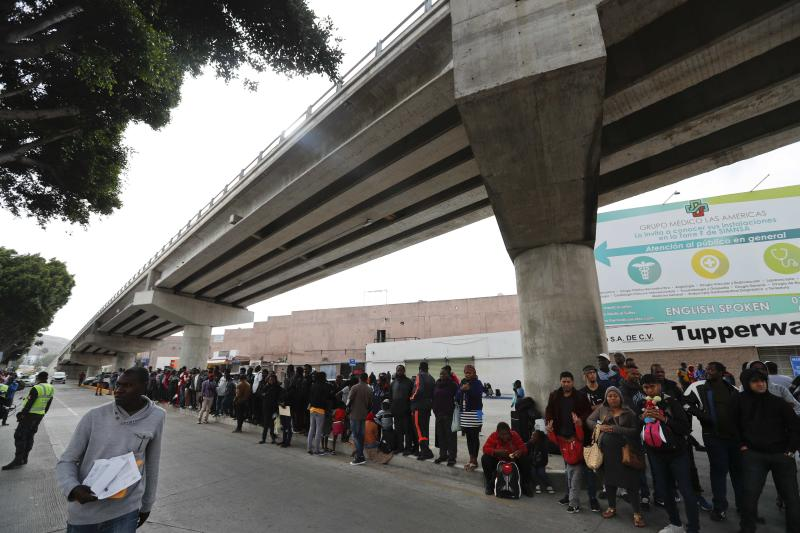 Migrants wait under a bridge to be attended to apply for asylum in the U.S., on the border in Tijuana, Mexico, Sunday, June 9, 2019. The mechanism that allows the U.S. to send migrants seeking asylum back to Mexico to await resolution of their process has been running in Tijuana since January. (AP Photo/Eduardo Verdugo)