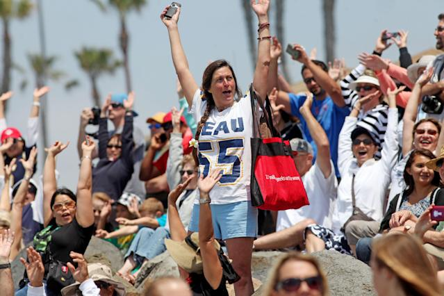 "OCEANSIDE, CA - MAY 6: Bryn Best waves to surfers in the water during a ""paddle-out"" ceremony in honor of NFL star Junior Seau on May 6, 2012 in Oceanside, California. Seau, who played for various NFL teams including the San Diego Chargers, Miami Dolphins and New England Patriots was found dead in his home on May 2nd of an apparent suicide. Family members have decided to donate his brain for research on links between concussions and possible depression. (Photo by Sandy Huffaker/Getty Images)"