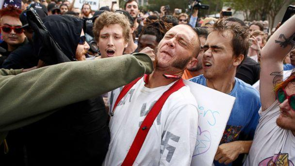 PHOTO: A man wearing a shirt with swastikas on it is punched by an unidentified member of the crowd near the site of a planned speech by white nationalist Richard Spencer at the University of Florida campus, Oct. 19, 2017, in Gainesville, Florida. (Brian Blanco/Getty Images)