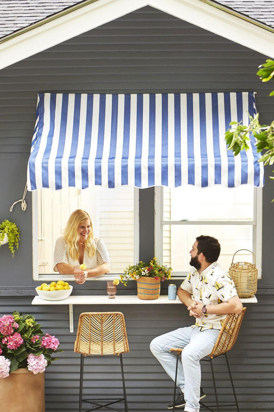 <p>Keep party guests out of the kitchen with this DIY serving station. Simply install a serving ledge under a window and dress the space with weather-resistant bar stools and a patterned awning. </p>