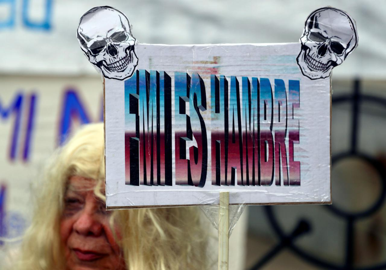"""A woman holds up a sign that reads """"IMF (International Monetary Fund) is hunger"""" during a protest against the government's austerity measures outside the Congress in Buenos Aires, Argentina September 17, 2018. REUTERS/Marcos Brindicci"""