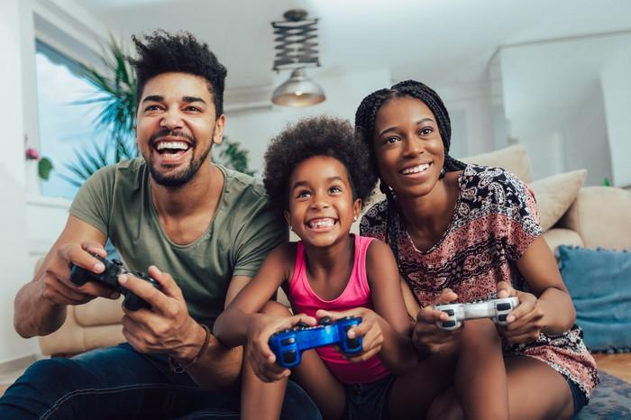 A man, a woman, and a child sit on a couch, holding video game controllers and smiling.