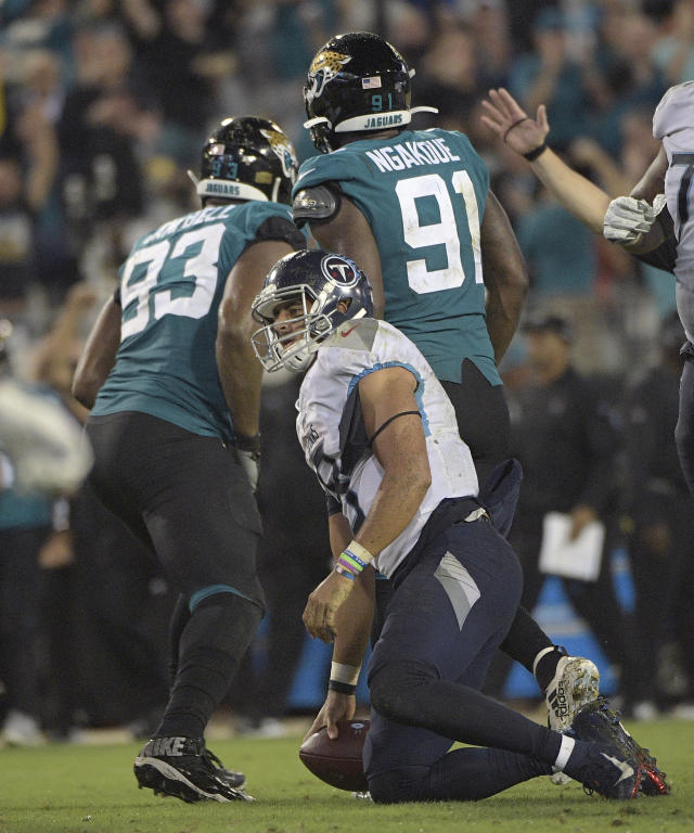 Tennessee Titans quarterback Marcus Mariota (8) gets up after being stopped by Jacksonville Jaguars defensive end Calais Campbell (93) and defensive end Yannick Ngakoue (91) on a fourth down play during the second half of an NFL football game Thursday, Sept. 19, 2019, in Jacksonville, Fla. (AP Photo/Phelan Ebenhack)