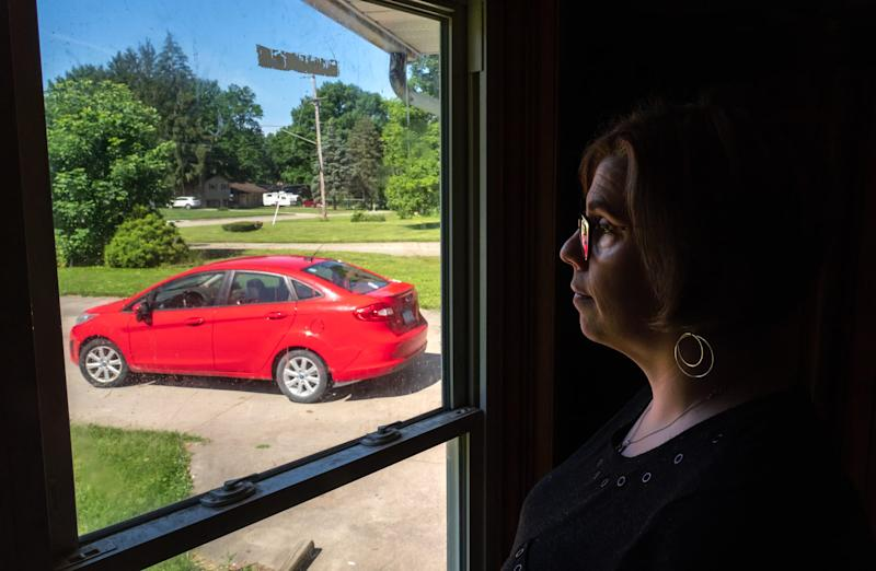 Michelle Hughes looks out the window towards her 2012 Ford Fiesta parked at her home in Flint on Wednesday, June 26, 2019.