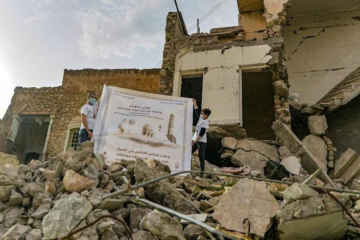 Youths unfurl a poster welcoming Pope Francis above the rubble of a destroyed house next to the ruins of the Syriac Catholic Church of the Immaculate Conception (al-Tahira) in Mosul, a northern Iraqi city ravaged by the Islamic State group