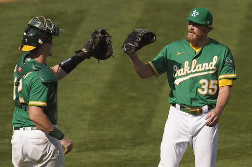 Oakland Athletics catcher Sean Murphy, left, celebrates with pitcher Jake Diekman after the Athletics defeated the Chicago White Sox 5-3 in Game 2 of an American League wild-card baseball series Wednesday, Sept. 30, 2020, in Oakland, Calif. (AP Photo/Eric Risberg)
