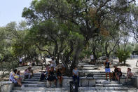 Tourists sit in the shade outside the ancient Acropolis, in Athens Greece, Tuesday, Aug. 3, 2021. Authorities in Greece have closed the Acropolis and other ancient sites during afternoon hours as a heatwave scorching the eastern Mediterranean continued to worsen. Temperatures reached 42 C (107.6 F) in parts of the Greek capital, as the extreme weather fueled deadly wildfires in Turkey and blazes across the region. (AP Photo/Michael Varaklas)