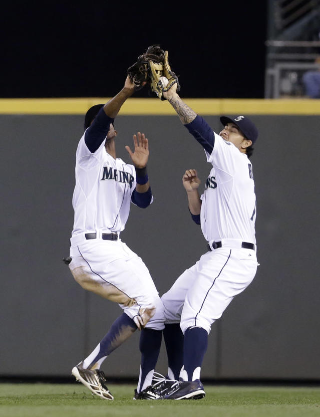 Seattle Mariners right fielder Stefen Romero, right, catches a fly ball just ahead of center fielder James Jones from Texas Rangers' Robinson Chirinos in the fourth inning of a baseball game Saturday, June 14, 2014, in Seattle. Romero held on for the out. (AP Photo/Elaine Thompson)