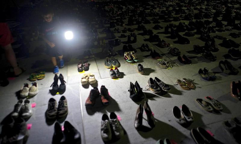 A child shines a light on hundreds of shoes at a memorial for those killed by Hurricane Maria, in front of the capitol in San Juan.