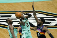 Charlotte Hornets guard Terry Rozier shoots over Phoenix Suns center Deandre Ayton and center Bismack Biyombo looks on during the first half of an NBA basketball game on Sunday, March 28, 2021, in Charlotte, N.C. (AP Photo/Chris Carlson)
