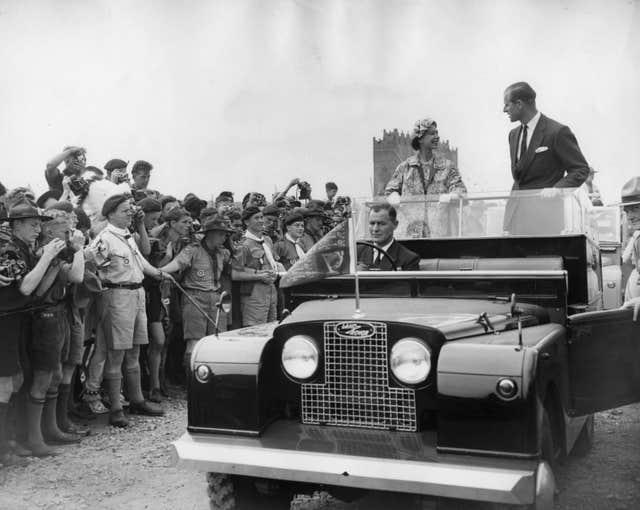 The Queen and the Duke of Edinburgh drive in an open Land Rover