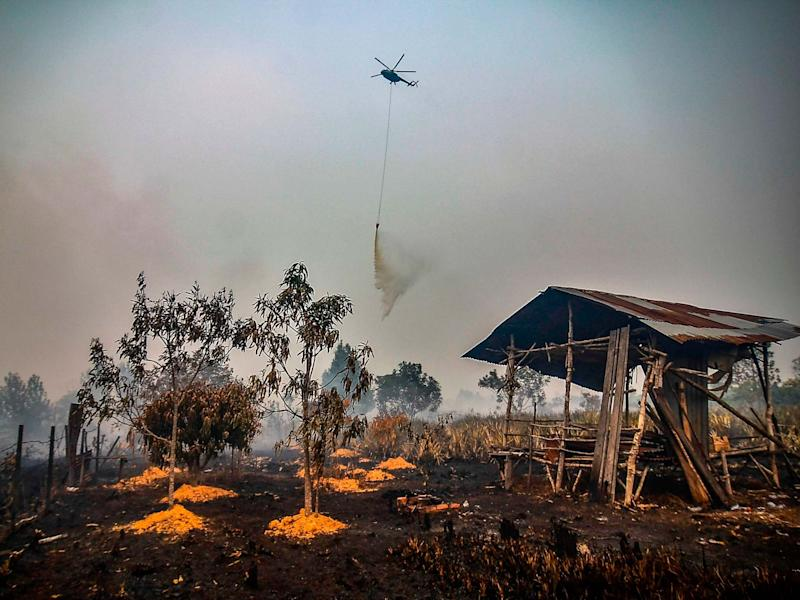 A water-bombing helicopter douses the burning peatland in Kampar of Riau province on 18 September 2019: Wahyudi/AFP/Getty Images