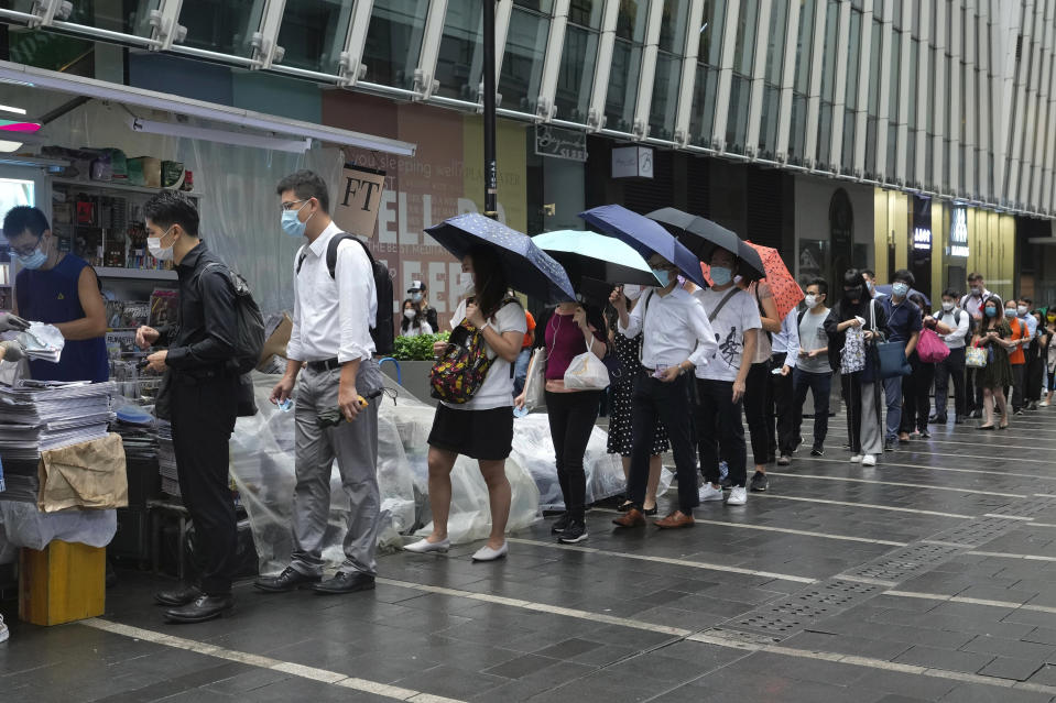 People queue up to buy last issue of Apple Daily at a newspaper booth at a downtown street in Hong Kong, Thursday, June 24, 2021. Hong Kong's sole remaining pro-democracy newspaper has published its last edition. Apple Daily was forced to shut down Thursday after five editors and executives were arrested and millions of dollars in its assets were frozen as part of China's increasing crackdown on dissent in the semi-autonomous city. (AP Photo/Vincent Yu)