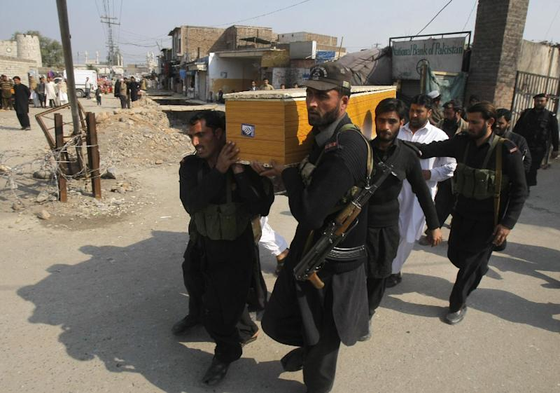 Pakistani security personnel carry the body of a fellow officer, who was killed in Saturday bomb blasts during their funeral procession, in Jamrud, near Peshawar, Pakistan, Saturday, March 1, 2014. The Pakistani Taliban announced Saturday that the group will observe a one-month cease-fire as part of efforts to negotiate a peace deal with the government, throwing new life into a foundering peace process. The violence Saturday showed how difficult it could be to enforce a cease-fire, let alone forge a peace agreement. (AP Photo/Mohammad Sajjad)