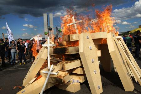 Striking police officers set fire to coffins during a protest by Police officers from several Brazilian states against pension reforms proposed by Brazil's president Michel Temer, in Brasilia, Brazil April 18, 2017. REUTERS/Adriano Machado