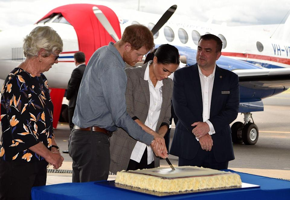 <p>At Dubbo Regional Airport in Australia, the Duke and Duchess of Sussex cut a cake celebrating 90 years of the nation's Royal Flying Doctor Service. </p>