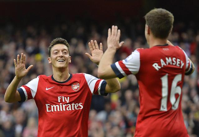 "Arsenal's Mesut Ozil (L) celebrates scoring his second goal against Norwich City with team-mate Aaron Ramsey during their English Premier League soccer match at the Emirates Stadium in London, October 19, 2013. REUTERS/Toby Melville (BRITAIN - Tags: SPORT SOCCER) NO USE WITH UNAUTHORIZED AUDIO, VIDEO, DATA, FIXTURE LISTS, CLUB/LEAGUE LOGOS OR ""LIVE"" SERVICES. ONLINE IN-MATCH USE LIMITED TO 45 IMAGES, NO VIDEO EMULATION. NO USE IN BETTING, GAMES OR SINGLE CLUB/LEAGUE/PLAYER PUBLICATIONS. FOR EDITORIAL USE ONLY. NOT FOR SALE FOR MARKETING OR ADVERTISING CAMPAIGNS"
