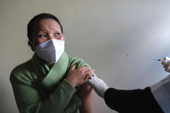 """Shimray Wungreichon, 43, looks at the nurse administering her the COVID-19 vaccine at the District Hospital in Ukhrul, in the northeastern Indian state of Manipur, Saturday, Jan. 16, 2021. """"I am very positive about it,"""" said Wungreichon, a nurse for 14 years who described getting vaccinated as a """"normal routine"""" for her. (AP Photo/Yirmiyan Arthur)"""