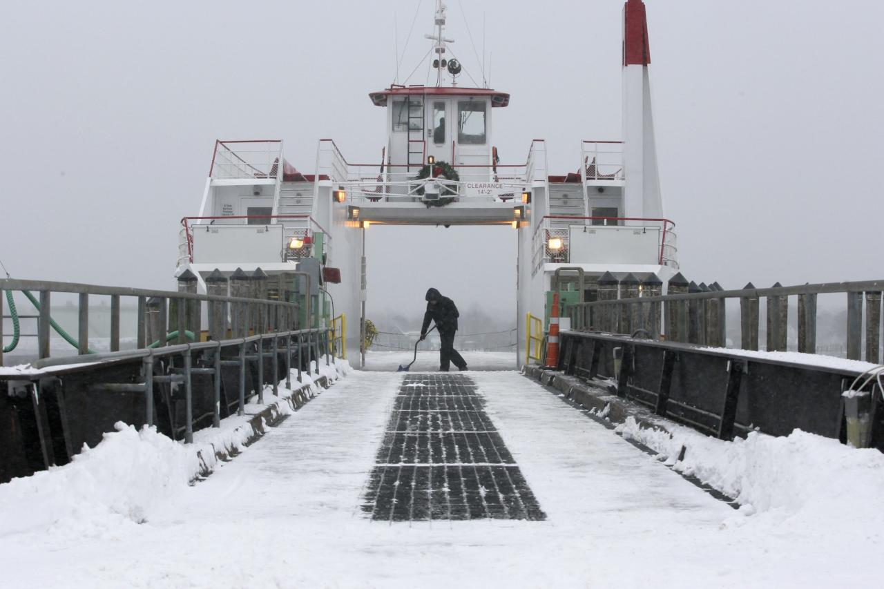Casco Bay Lines deckhand Nick Ferrara shovels off the deck of the car ferry Machigonne II following a snowstorm in Portland, Maine December 15, 2013. Another round of wintry weather battered the U.S. Midwest and East Coast on Saturday as a massive storm spanning more than 1,000 miles (2,540 km) dumped heavy snow, snarling air traffic and making roads treacherous. REUTERS/Joel Page (UNITED STATES - Tags: SOCIETY ENVIRONMENT)