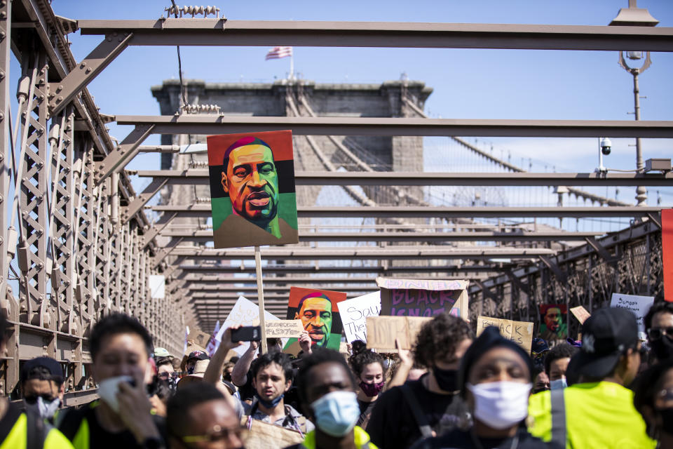 """MANHATTAN, NY - JUNE 19:  Thousands of protesters walk in a peaceful protest across the Brooklyn Bridge holding signs and painted portraits of George Floyd and a protester in the foreground with a raised fist with the Brooklyn Bridge Arch in the background.  This was part of the Unite NY 2020, Bringing all of New York Together rally and march as protests that happened around the country to celebrate Juneteenth day which marks the end of slavery in the United States. Protesters continue taking to the streets across America and around the world after the killing of George Floyd at the hands of a white police officer Derek Chauvin that was kneeling on his neck during for eight minutes, was caught on video and went viral.  During his arrest as Floyd pleaded, """"I Can't Breathe"""". The protest are attempting to give a voice to the need for human rights for African American's and to stop police brutality against people of color.  They are also protesting deep-seated racism in America.   Many people were wearing masks and observing social distancing due to the coronavirus pandemic.  Photographed in the Manhattan Borough of New York on June 19, 2020, USA.  (Photo by Ira L. Black/Corbis via Getty Images)"""