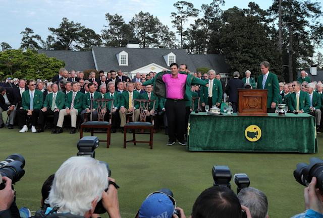 Sergio Garcia of Spain (rear), last year's Masters' champion, helps put the Green Jacket on 2018 Masters winner Patrick Reed following final round play of the 2018 Masters golf tournament at the Augusta National Golf Club in Augusta, Georgia, U.S. April 8, 2018. REUTERS/Lucy Nicholson